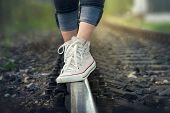 Girl Walking On Railway Track. Close Up Of Legs Walking On Railway Tracks. Railway Tracks. Female Le poster