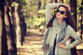 Beautiful smiling girl in stylish fashion clothes in autumn Park.  Beautiful woman outdoors in sunny poster