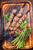 Traditional Russian shashlik on a barbecue skewer with green asparagus and paprika as top view on a  poster
