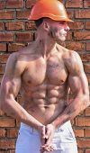 Builder With Muscular Torso And Helmet, Brick Wall On Background. Athlete Posing With Sexy Nude Tors poster