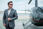 Businessman near private helicopter poster