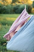 Pink And Blue Bedding Sheet On Forest Background Under The Bright Warm Sun. Clean Bed Sheet Hanging  poster