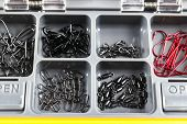 Opened Tackle Box With Fishing Hooks And Accessories. Fishing Hooks In Box Sections. Case For Tackle poster
