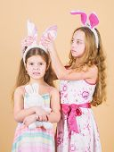 Putting Bunny Ears On. Cute Children In Easter Bunny Style Holding Hearts. Happy Children Celebratin poster