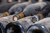 Closeup Dark Dusty Wine Bottles With Old Crumbly Cork. Long Aging, Musty Winery Vault, Rare Ancient  poster