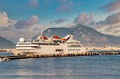 Cruise Ship Docked In The Port Of Tropical Country. Vessel In Front Of Sunset With Mountain Range. poster