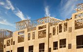 A New Apartment Complex Being Framed With Wood And Plywood Lumber poster