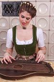pic of autoharp  - Young Bavarian girl in traditional dress plays music on a zither - JPG