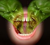 foto of eminent  - Bad breath as garlic smell eminating from inside a human mouth as a health concept of an offensive foul odour caused by smoking or eating with a green gas shaped as evil faces over an open human mouth - JPG