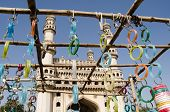 image of charminar  - View looking through a market stall selling bangles towards the landmark Charminar tower in Hyderabad - JPG