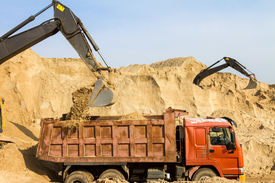 stock photo of dumper  - Excavator Loading Dumper Truck at Construction Site - JPG