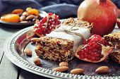 pic of roughage  - Granola bars on plate with nuts pomegranate and dried fruits on wooden background - JPG