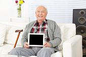 Senior man holding tablet computer with empty black display