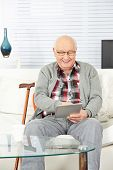 Senior man using tablet computer at home in the living room