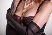 Close-up shot of a busty woman in vintage red bra, sheer gloves and pearl necklace