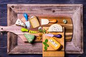 image of penicillium  - English and French cheese on wooden boards knives for cheese - JPG