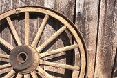 picture of wagon  - Wooden wagon wheel leaning against weathered barn - JPG