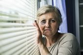 stock photo of bruises  - Scared woman is looking through the window - JPG