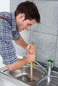 image of plunger  - Young Handsome Man Using Plunger In Kitchen Sink