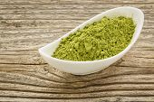 foto of moringa oleifera  - moringa leaf powder in a small ceramic bowl against grained wood - JPG