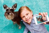 stock photo of memory stick  - little girl taking photo of herself and her dog with mobile phone camera - JPG