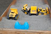 stock photo of dump_truck  - A bright yellow dump truck plastic toy in a raised wooden sand box with other plastic toys around it - JPG