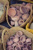 foto of handicrafts  - Rustic handmade ceramic clay brown terracotta cups souvenirs at street handicraft market in gafsa - JPG