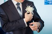 image of boutonniere  - groom trying his white boutonniere trying to wedding jacket - JPG