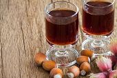 picture of hazelnut  - Homemade Hazelnut liqueur in two glasses and hazelnuts of an old rustic wooden table - JPG