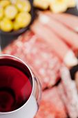 picture of charcuterie  - Glass of red wine with charcuterie assortment on the background - JPG
