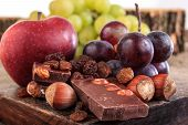 picture of mixed nut  - Bunch of fruit apples and grapes with nuts chocolate Chocolate with nuts raisins apple and grapes on wooden background - JPG