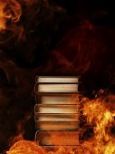 pic of hardcover book  - Conceptual image of a tall stack of hardcover books in a burning fire with flames and smoke swirling around them in a darkened room with copyspace - JPG