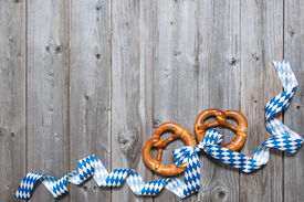 stock photo of pretzels  - Bavarian pretzels with ribbon on wooden board as a background for Oktoberfest - JPG