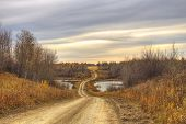 image of dirt road  - Winding dirt road through a valley between ponds of water in autumn - JPG