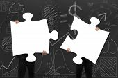 foto of comrades  - Two business people assembling blank white jigsaw puzzles on business concept doodles background - JPG