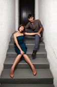 picture of office romance  - Happy young couple sitting on the steps in office - JPG