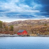 image of red barn  - Traditional Norwegian red wooden boat barn with crane on the seacoast - JPG