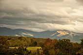 stock photo of appalachian  - The beautiful Appalachian mountains in West Virginia during autumn colors as the sun highlights the clouds - JPG