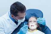 pic of dentist  - Male dentist examining girls teeth in the dentists chair - JPG