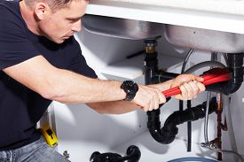 image of handyman  - Plumber man with tools in the kitchen - JPG