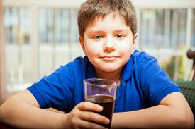 stock photo of tween  - Pretty blond tween enjoying a glass of soda at home and smiling - JPG