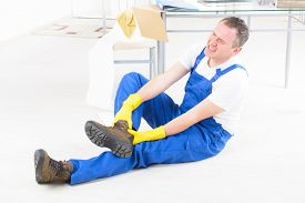 foto of unsafe  - Man worker with ankle injury - JPG