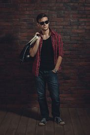 image of denim wear  - Young hipster man wearing sunglasses casual clothes unbuttoned shirt and denim jeans with bag over shoulder standing near brick wall with hand in the pocket and looking away - JPG