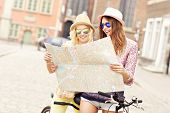 foto of tandem bicycle  - A picture of two girl friends using a map and riding a tandem bicycle in the city - JPG