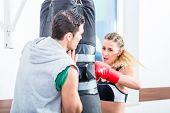 foto of sandbag  - Young woman with trainer in boxing sparring hitting sandbag - JPG