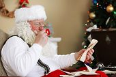 stock photo of letters to santa claus  - Santa Claus sitting with children letters in comfortable chair near fireplace at home - JPG