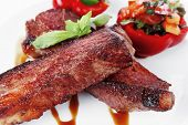 stock photo of braai  - fresh red beef meat steak barbecue garnished vegetable salad and basil  in half of pepper bell on white plate isolated over white background - JPG