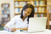pretty female college student studying in library poster