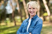stock photo of close-up middle-aged woman  - beautiful middle aged woman with arms folded outdoors - JPG
