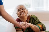 pic of old lady  - Happy old lady holding a hand of her husband and looking at him - JPG